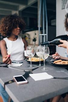 Jovem mulher africana bebendo vinho no restaurante moderno com amigos