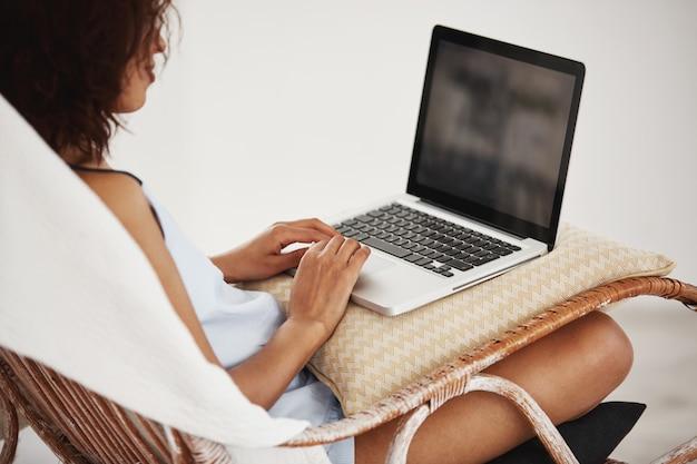 Jovem mulher africana bonita no perfil sorrindo sentado com o laptop na cadeira.