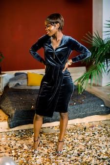 Jovem mulher africana comemorando o ano novo ou um evento., animado e feliz em pé na sala elegante com confetes no chão.