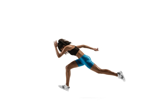 Jovem mulher africana correndo isolado no fundo branco do estúdio. uma corredora ou atleta feminina. silhueta de atleta de corrida