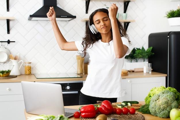 Jovem mulher africana está dançando e ouvindo música através de fones de ouvido com os olhos fechados na cozinha