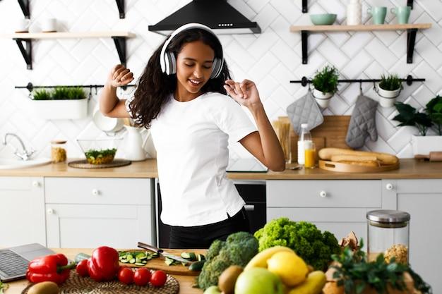 Jovem mulher africana está dançando e ouvindo música através de fones de ouvido na cozinha