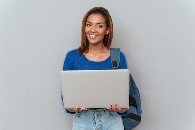 Jovem mulher africana feliz em suéter e jeans com mochila segurando o laptop nas mãos. fundo cinza isolado