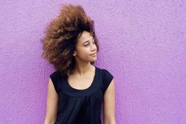 Jovem mulher africana pensando e olhando para longe