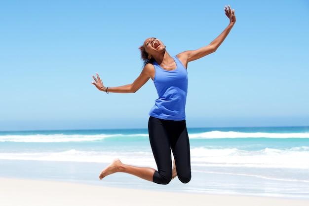Jovem mulher africana pulando de alegria na praia