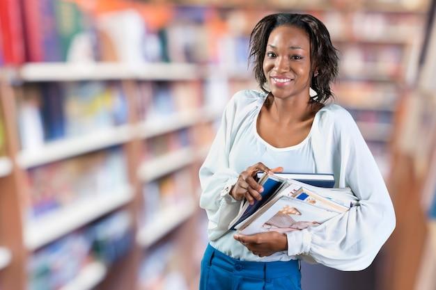 Jovem mulher africana segurando a pilha de revistas
