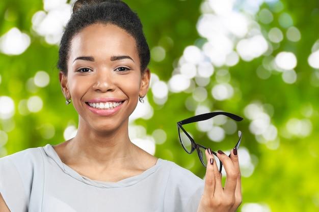 Jovem mulher africana segurando seus óculos
