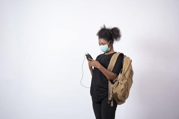 Jovem mulher africana usando uma máscara facial e seu telefone celular