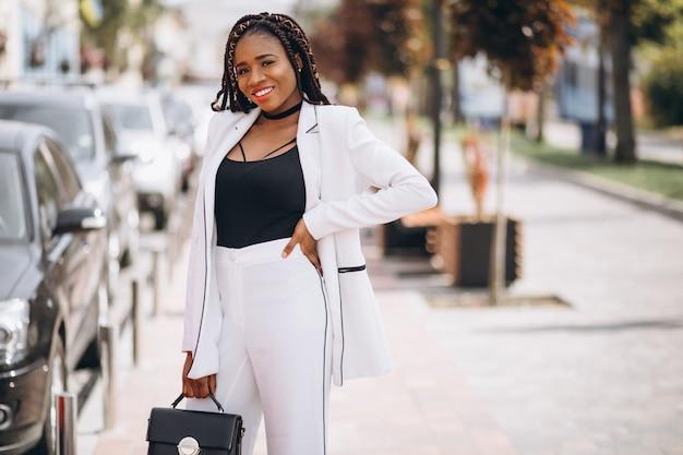 Jovem mulher africana vestida de terno branco do lado de fora da rua