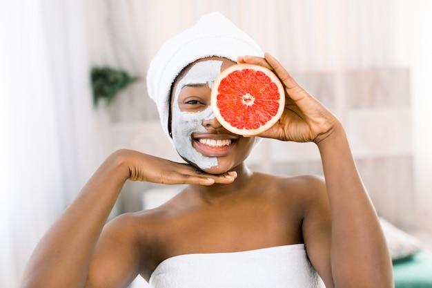 Jovem mulher africana, vestindo uma toalha com uma máscara purificadora no rosto, segurando a toranja cítrica no spa