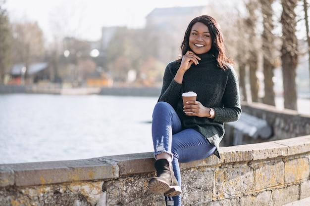 Jovem mulher afro-americana a beber café à beira do lago
