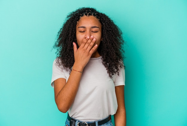 Jovem mulher afro-americana a bocejar, mostrando um gesto cansado, cobrindo a boca com a mão.