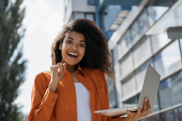 Jovem mulher afro-americana animada usando laptop, segurando o dedo, tendo uma idéia