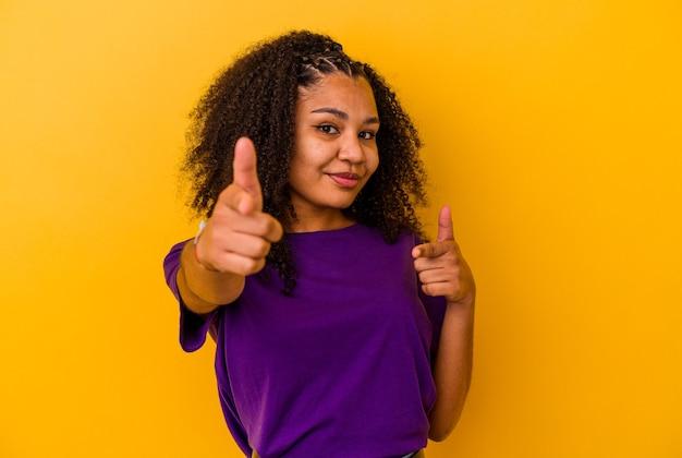 Jovem mulher afro-americana, apontando para a frente com os dedos.