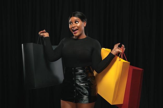 Jovem mulher afro-americana às compras com embalagens coloridas na parede preta.