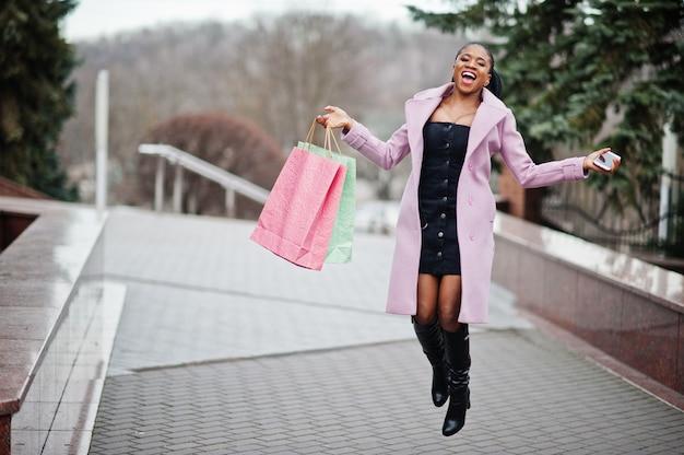 Jovem mulher afro-americana bonita elegante na rua, vestindo casaco de roupa de moda com sacolas e telefone celular nas mãos.