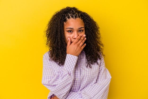 Jovem mulher afro-americana, cobrindo a boca com as mãos, parecendo preocupada.