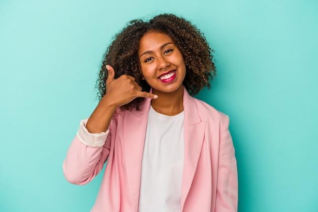 Jovem mulher afro-americana com cabelo encaracolado, isolado em um fundo azul, mostrando um gesto de chamada de celular com os dedos.