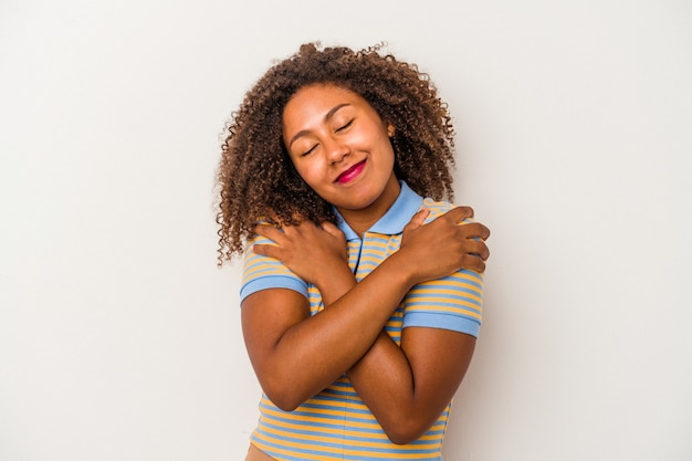 Jovem mulher afro-americana com cabelo encaracolado, isolado no fundo branco abraços, sorrindo despreocupada e feliz.