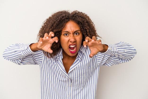 Jovem mulher afro-americana com cabelo encaracolado, isolado no fundo branco, mostrando garras imitando um gato, gesto agressivo.