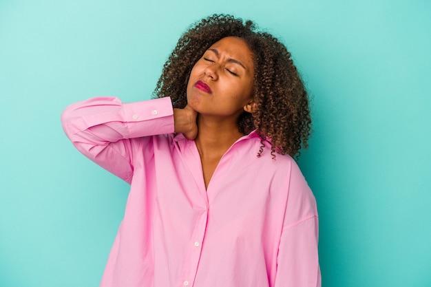 Jovem mulher afro-americana com cabelos cacheados, isolado em um fundo azul, cansada e com muito sono, mantendo a mão na cabeça.