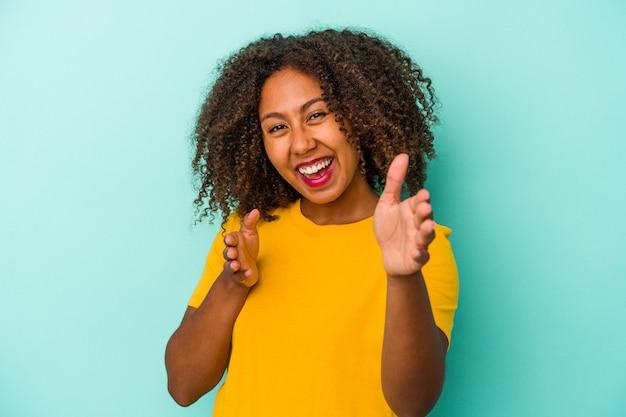 Jovem mulher afro-americana com cabelos cacheados, isolado em um fundo azul, sente-se confiante em dar um abraço para a câmera.