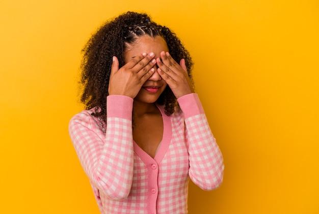Jovem mulher afro-americana com medo de cobrir os olhos com as mãos.