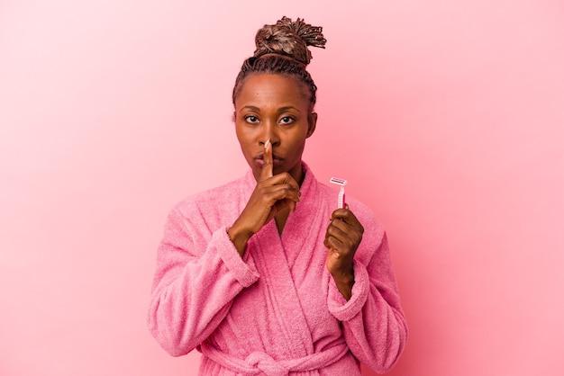 Jovem mulher afro-americana com roupão rosa segurando a lâmina de barbear isolada no fundo rosa, mantendo um segredo ou pedindo silêncio.