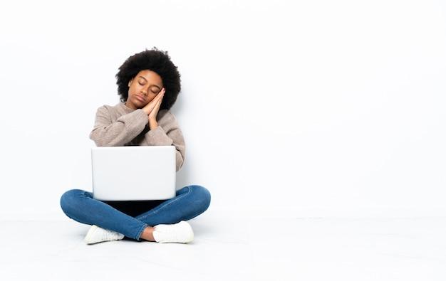 Jovem mulher afro-americana com um laptop sentado no chão, fazendo o gesto do sono em expressão dorable