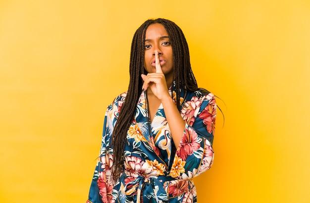Jovem mulher afro-americana com um pijama asiático isolada a guardar um segredo ou a pedir silêncio.