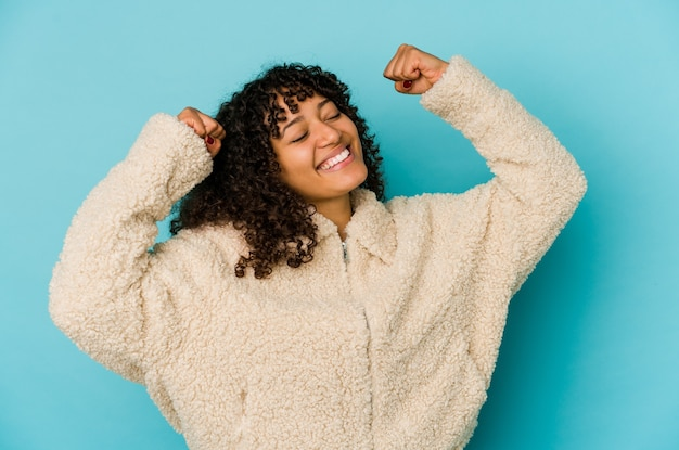 Jovem mulher afro-americana comemorando um dia especial, pula e levanta os braços com energia.