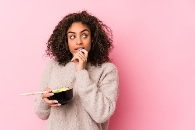 Jovem mulher afro-americana comendo macarrão relaxada pensando em algo olhando para um espaço de cópia.