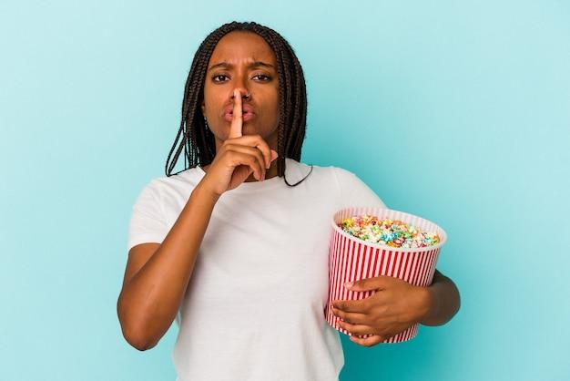 Jovem mulher afro-americana comendo pipocas isoladas em um fundo azul, mantendo um segredo ou pedindo silêncio.