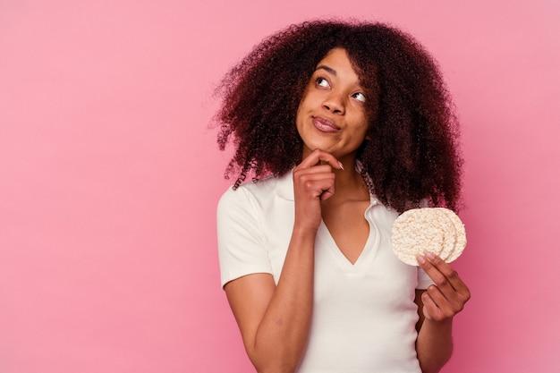 Jovem mulher afro-americana comendo um bolo de arroz isolado no fundo rosa, olhando de soslaio com expressão duvidosa e cética.