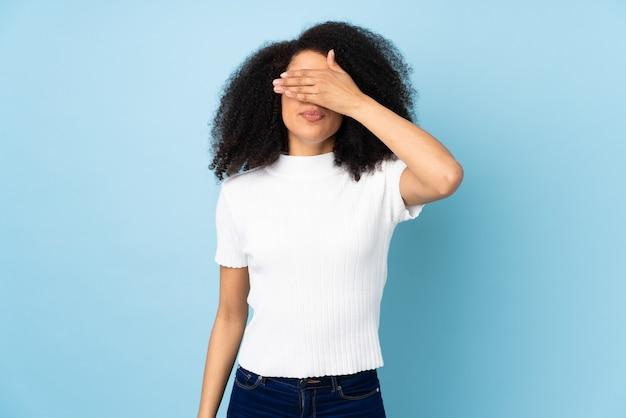 Jovem mulher afro-americana coning os olhos pelas mãos. não quero ver nada