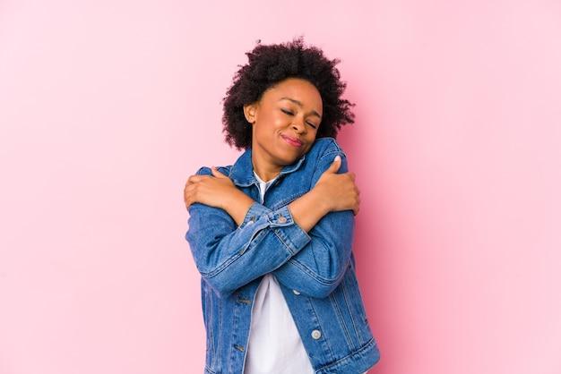 Jovem mulher afro-americana contra um fundo rosa isolado abraços, sorrindo despreocupada e feliz.