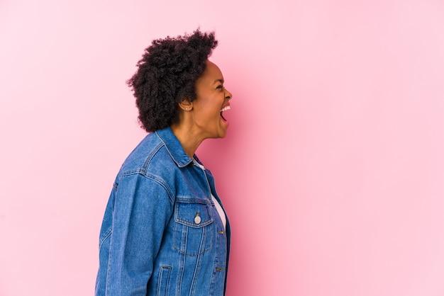 Jovem mulher afro-americana contra um fundo rosa isolado gritando para um espaço de cópia