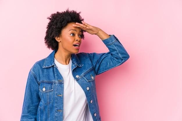 Jovem mulher afro-americana contra um fundo rosa isolado, olhando para longe, mantendo a mão na testa.