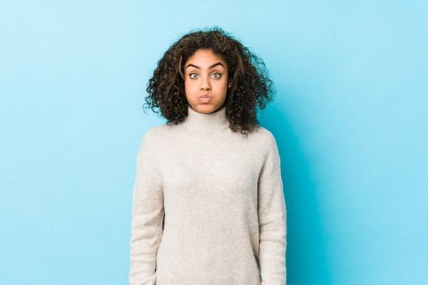 Jovem mulher afro-americana de cabelos cacheados sopra as bochechas, tem expressão cansada