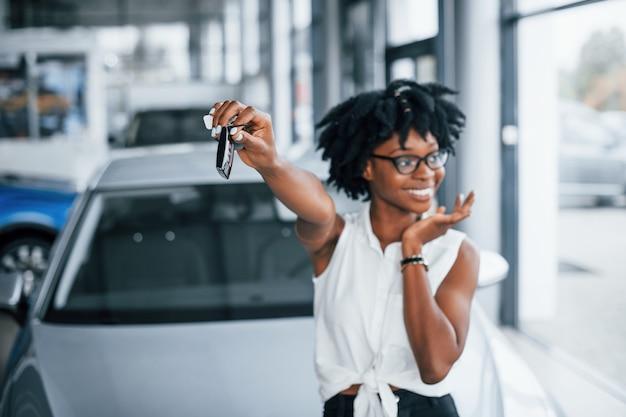 Jovem mulher afro-americana de óculos fica dentro de casa com as chaves nas mãos.