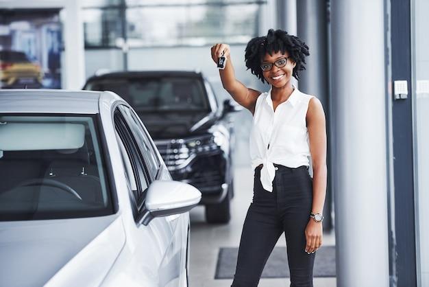 Jovem mulher afro-americana de óculos fica no salão do carro perto do veículo com as chaves nas mãos.