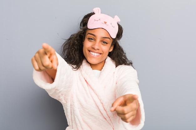 Jovem mulher afro-americana de pijama e uma máscara de dormir sorrisos alegres apontando para a frente.