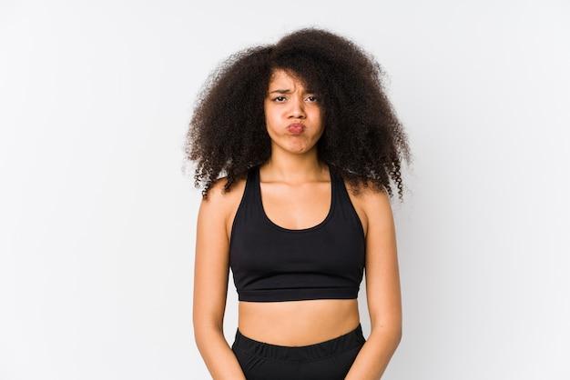Jovem mulher afro-americana desportiva sopra as bochechas, tem expressão cansada. conceito de expressão facial.