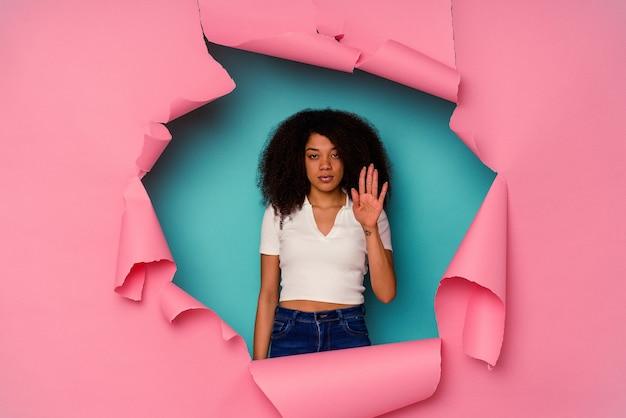 Jovem mulher afro-americana em papel rasgado, isolada em pé azul com a mão estendida, mostrando o sinal de pare, impedindo você.