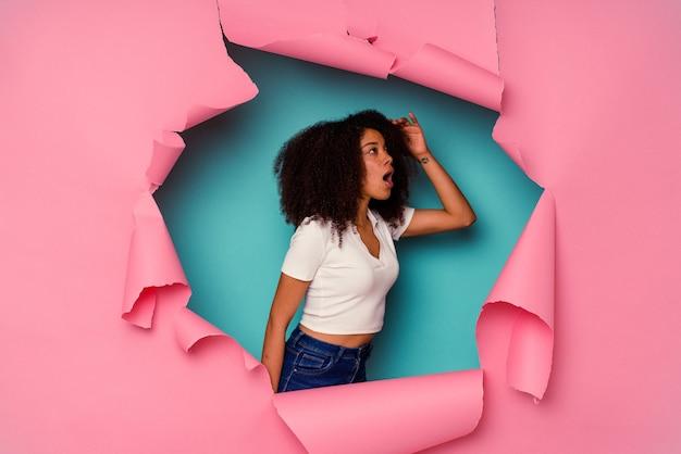Jovem mulher afro-americana em papel rasgado, isolado em azul, olhando para longe, mantendo a mão na testa.