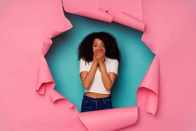 Jovem mulher afro-americana em papel rasgado, isolado em um fundo azul, chocada, cobrindo a boca com as mãos.