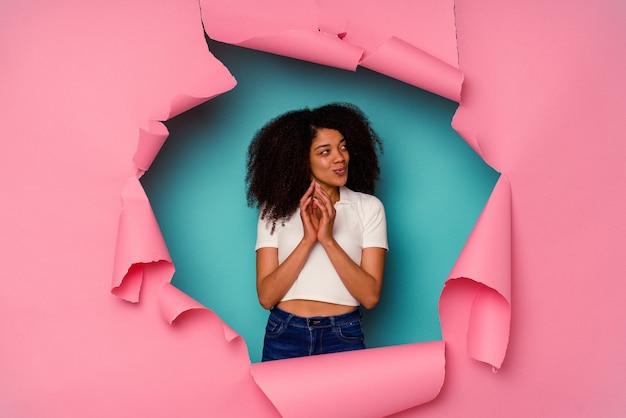 Jovem mulher afro-americana em papel rasgado, isolado em um fundo azul, fazendo o plano em mente, criando uma ideia.