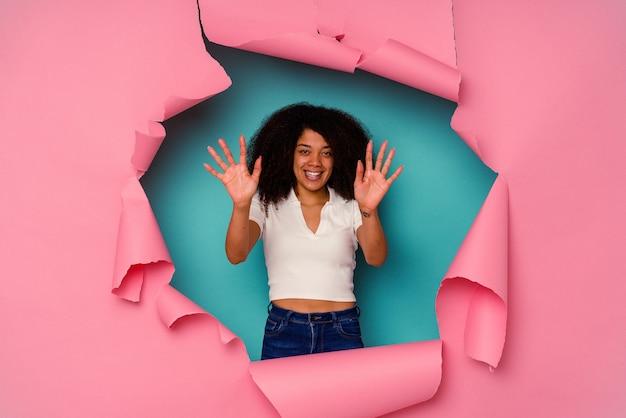 Jovem mulher afro-americana em papel rasgado, isolado em um fundo azul, mostrando o número dez com as mãos.