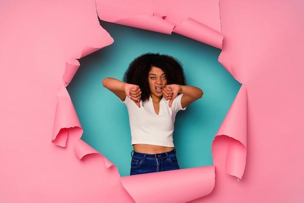 Jovem mulher afro-americana em papel rasgado, isolado em um fundo azul, mostrando o polegar para baixo e expressando antipatia.