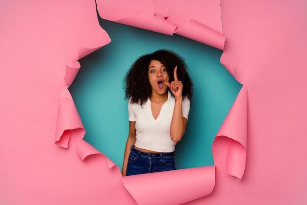 Jovem mulher afro-americana em papel rasgado, isolado em um fundo azul, tendo uma ideia, o conceito de inspiração.